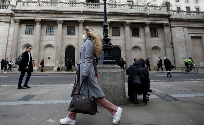 A woman, wearing a protective face mask, walks in front of the Bank of England, following an outbreak of the coronavirus, in London