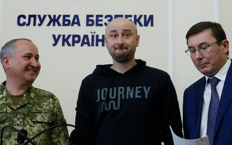 """Arkady Babchenko, the Russian journalist reportedly murdered in Kiev, faked his death as part of a sting operation to """"expose Russian agents"""" who were plotting his killing, Ukrainian officials have said. The 41-year-old appeared at a press conference alongside the head of the Ukrainian security service on Wednesday afternoon. Mr Babchenko, who was visibly tearful, said: """"Special apologies to my wife. Olechka, I am sorry, but there were no options here. """"The operation took two months to prepare. I was told a month ago. As a result of the operation, one person has been captured, he is being held."""" Vasily Gritsak, head of the Ukrainian Security Service (SBU), said the sting had been set up in order to thwart a genuine plot against Mr Babchenko's life. Arkady Babchenko, centre, told a Press conference in Kiev the reported murder was part of sting operation to catch a hit squad Credit: VALENTYN OGIRENKO /Reuters """"I can now reveal details of the SBU special operation, thanks to which we were able not only to thwart a cynical provocation, but also document the Russian special service's preparations for this low crime,"""" Mr Gritsak told journalists in Kiev. """"I could offer my condolences to to Arkady Babchenko's family, but I will not. On the contrary, today I congratulate Arkady on his third birthday in this hall,"""" he added before Mr Babchenko entered the room. Mr Babchenko has previously described a narrow escape with death while reporting the war in Ukraine in 2014 as his """"second birthday."""" Mr Babchenko's death was announced late on Tuesday night and sent shockwaves through the Russian journalistic community. Arkady Babchenko was a fierce critic of Vladimir Putin Credit: Vitalii Nosach/Reuters Mr Babchenko, known for his sharp criticism of Vladimir Putin, was reported to have been found by his wife in a pool of blood at their Kiev apartment after apparently having been shot in the back. He died in the ambulance on the way to hospital, Ukrainian police earlier said. Ukraini"""