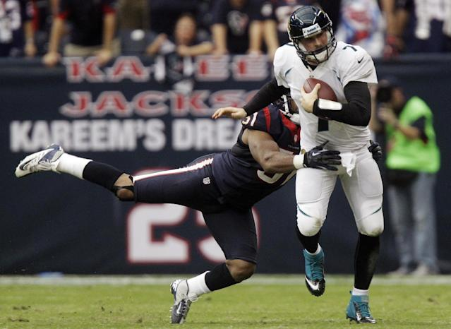 Jacksonville Jaguars quarterback Chad Henne (7) breaks a tackle by Houston Texans' Shiloh Keo (31) in overtime of an NFL football game, Sunday, Nov. 18, 2012, in Houston. The Texans won 43-37. (AP Photo/Patric Schneider)