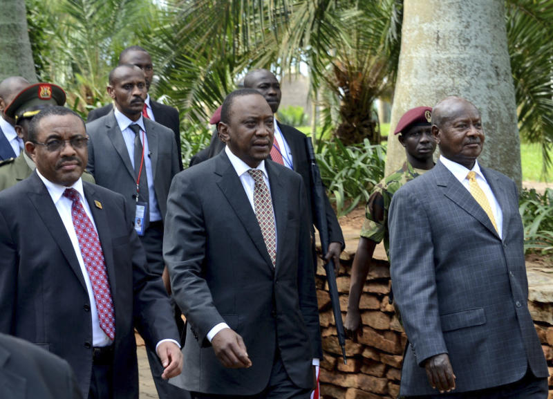 Ethiopia Prime Minister Hailemarian Desalegn, front left, walks with Kenya President Uhuru Kenyatta, centre, and Uganda President Yoweri Museveni, right, as they attend the closing meeting for the African Union Mission in Somalia AMISOM at Speke Resort Munyonyo in Uganda's capital Kampala, Sunday Aug. 4, 2013. Regional leaders say they want Somalia's central government to take control of Kismayo, a disputed port city that has been the scene of fighting between rival militias. (AP Photo/Stephen Wandera)