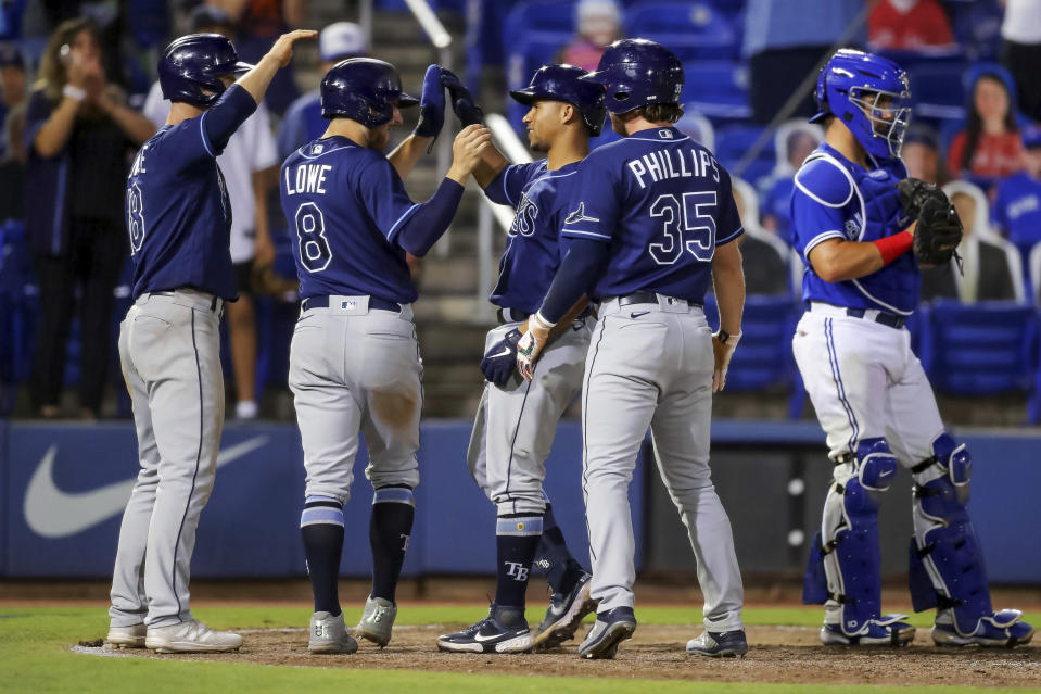 Tampa Bay Rays' Francisco Mejia, center, is congratulated by teammates Joey Wendle (18), Brandon Lowe (8) and Brett Phillips (35) as they celebrate his grand slam, next to Toronto Blue Jays catcher Reese McGuire during the 12th inning of a baseball game Friday, May 21, 2021, in Dunedin, Fla. The Rays won 9-7. (AP Photo/Mike Carlson)