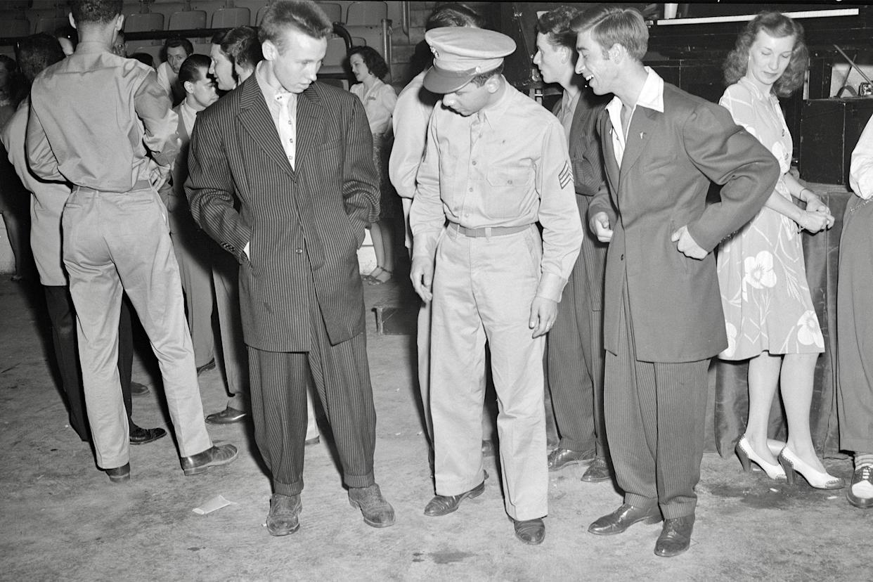 A soldier with two men wearing zoot suits in Washington, D.C., 1942