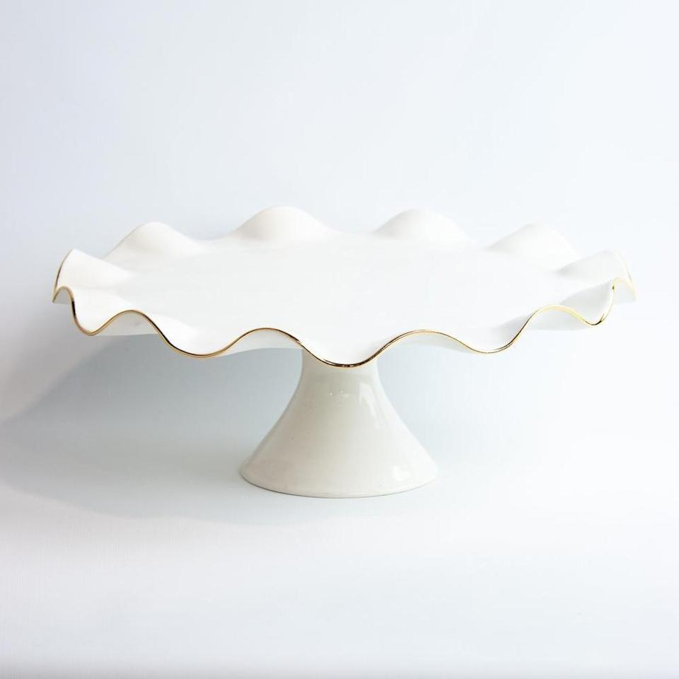 """<p><strong>Susan Gordon Pottery</strong></p><p>shopsusangordonpottery.com</p><p><strong>$188.00</strong></p><p><a href=""""https://shopsusangordonpottery.com/collections/serveware/products/cake-stand"""" rel=""""nofollow noopener"""" target=""""_blank"""" data-ylk=""""slk:Shop It"""" class=""""link rapid-noclick-resp"""">Shop It</a></p><p>Now her baked goods can shine like she does, thanks to this stunning handmade cake stand adorned with 22k gold luster overglaze on the edges. This cake stand is offered in dozens of colors and can be personalized for an extra-special touch. </p>"""