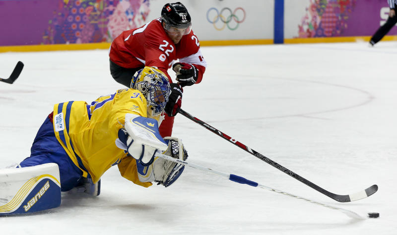 Sweden goaltender Henrik Lundqvist reaches to clear the puck away from Canada forward Jamie Benn during the second period of the men's gold medal ice hockey game at the 2014 Winter Olympics, Sunday, Feb. 23, 2014, in Sochi, Russia. (AP Photo/Julio Cortez)