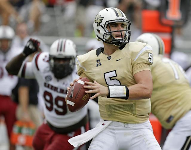 Central Florida quarterback Blake Bortles (5) throws a pass as he is chased by South Carolina defensive tackle Kelcy Quarles (99) during the first half of an NCAA college football game in Orlando, Fla., Saturday, Sept. 28, 2013.(AP Photo/John Raoux)
