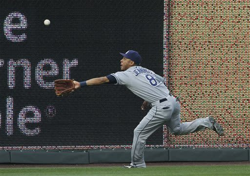 Tampa Bay Rays center fielder Desmond Jennings reaches to catch a fly ball hit by Kansas City Royals' Alex Gordon in the first inning of a baseball game at Kauffman Stadium in Kansas City, Mo., Wednesday, May 1, 2013. Jennings made the catch for the out. (AP Photo/Colin E. Braley)