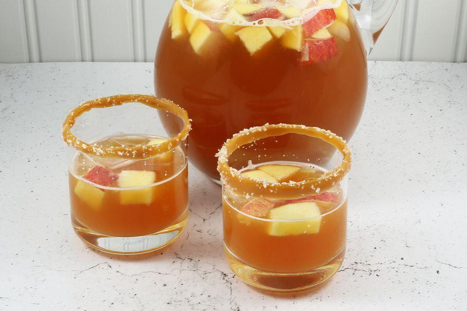 """<p> In a large pot, combine 1 gallon of apple cider, 2 liters of ginger ale, 1 cup of orange juice, 1 cup of caramel syrup, and 1/3 cup of lemon juice. Chill until ready to serve. Add 4 chopped apples and 4 cups of ice to the mixture. Finally, rim glasses with caramel ice cream topping and flaky salt before serving. </p><p><em>Recipe from <a href=""""https://www.thespruceeats.com/salted-caramel-apple-punch-4147280"""" rel=""""nofollow noopener"""" target=""""_blank"""" data-ylk=""""slk:The Spruce Eats."""" class=""""link rapid-noclick-resp"""">The Spruce Eats.</a></em> </p>"""