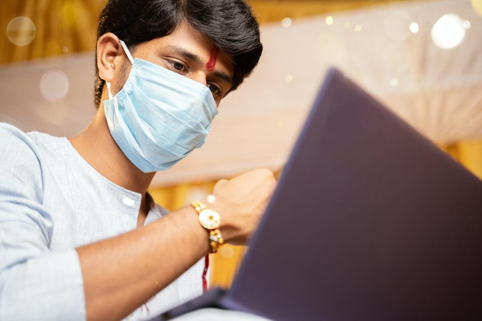 young man with medical mask making video call and showing Rakhi or Raksha Bandhan to his sister or family friends after festival ceremony during coronavirus ot covid-19 pandemic