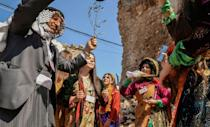 Young women dressed in traditional clothing celebrate the arrival of Pope Francis in Mosul's old city