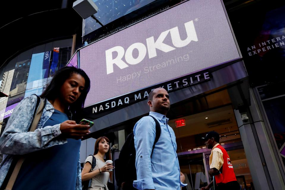 People pass by a video sign display with the logo for Roku Inc, a Fox-backed video streaming firm, that held it's IPO at the Nasdaq Marketsite in New York, U.S., September 28, 2017. REUTERS/Brendan McDermid
