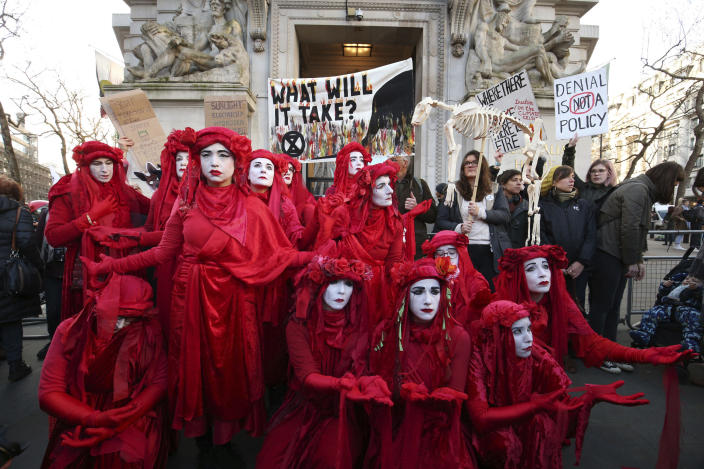 The Red Rebels join climate change protesters outside the Australian Embassy in London, where Extinction Rebellion are staging a protest against the Australian government's response to the wildfires in Australia, Friday Jan. 10, 2020. (Jonathan Brady/PA via AP)
