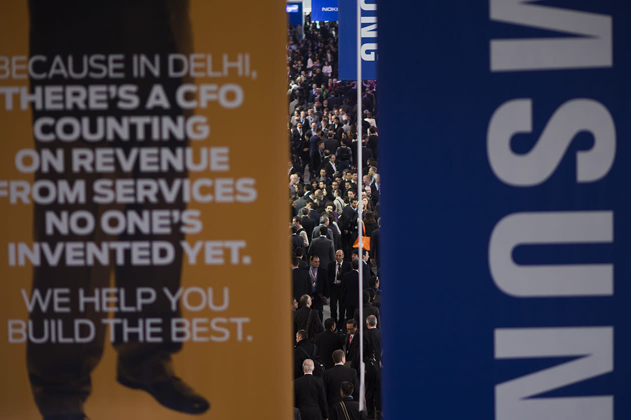 Visitors walk in one of the pavilions of the Mobile World Congress.