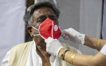 A health worker adjusts the face mask of an elderly person before administering COVISHIELD vaccine at the Guwahati Medical College hospital in Gauhati, India, Monday, March 1, 2021. India is expanding its COVID-19 vaccination drive beyond health care and front-line workers, offering the shots to older people and those with medical conditions that put them at risk. (AP Photo/Anupam Nath)