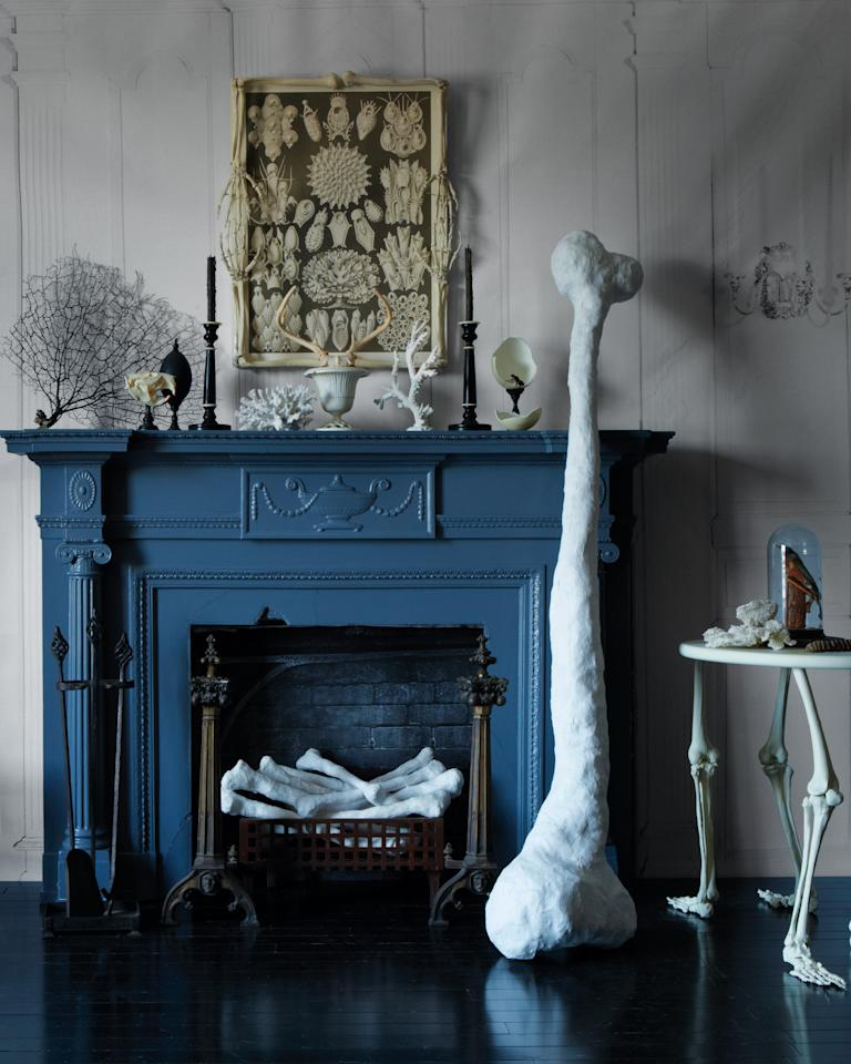 """<p>Go larger than life.&nbsp;This """"Flintstones""""-size femur and the heap of humeri posing as logs in the fireplace are made from newspaper wrapped in plaster cloth.</p>"""