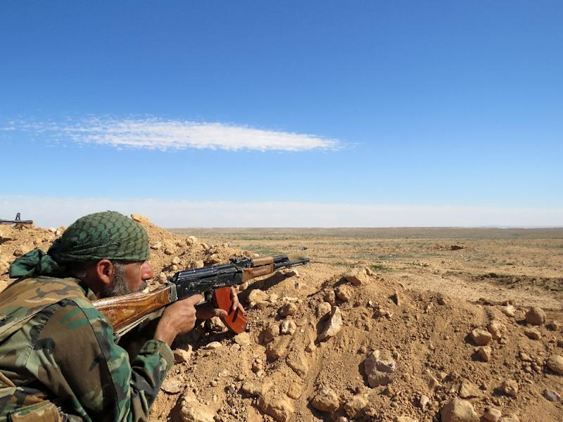 A Syrian soldier takes aim on the outskirts of Syria's Raqa region on February 19, 2016
