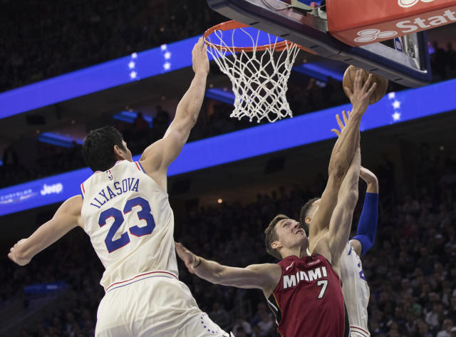 Miami Heat's Goran Dragic, center, of Slovania, gets his shot blocked by Philadelphia 76ers' Ben Simmons, right, of Australia, with Ersan Ilyasova, left, of Turkey, defending during the first half in Game 5 of a first-round NBA basketball playoff series, Tuesday, April 24, 2018, in Philadelphia. (AP Photo/Chris Szagola)