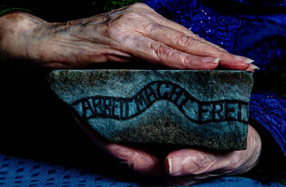 """Elizabeth Nussbaum returned to Auschwitz-Birkenau 18 years ago and brought back a stone from the train tracks there. She hired an artist to paint a rendering of the camp on it, along with the slogan above an entrance: """"Arbeit Macht Frie,"""" loosely translated as """"Work sets you free."""""""
