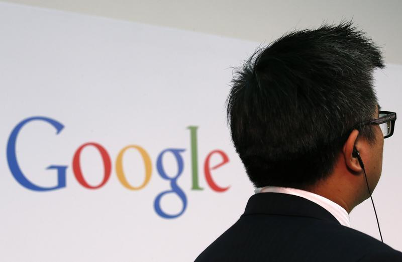 A man stands in front of a Google logo in Hong Kong