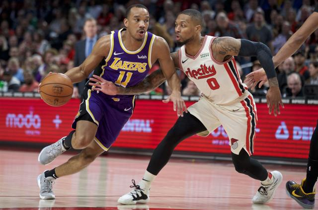 Los Angeles Lakers guard Avery Bradley, left, dribbles past Portland Trail Blazers guard Damian Lillard during the first half of an NBA basketball game in Portland, Ore., Saturday, Dec. 28, 2019. (AP Photo/Craig Mitchelldyer)