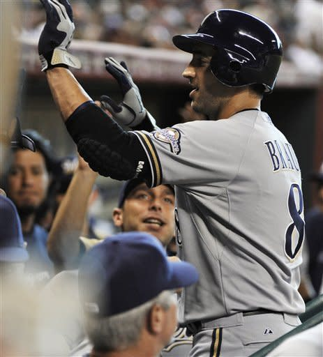 Milwaukee Brewers' Ryan Braun (8) is welcomed back to the dugout after hitting a solo home run against the Houston Astros in the first inning of a baseball game Friday, July 6, 2012, in Houston. (AP Photo/Pat Sullivan)