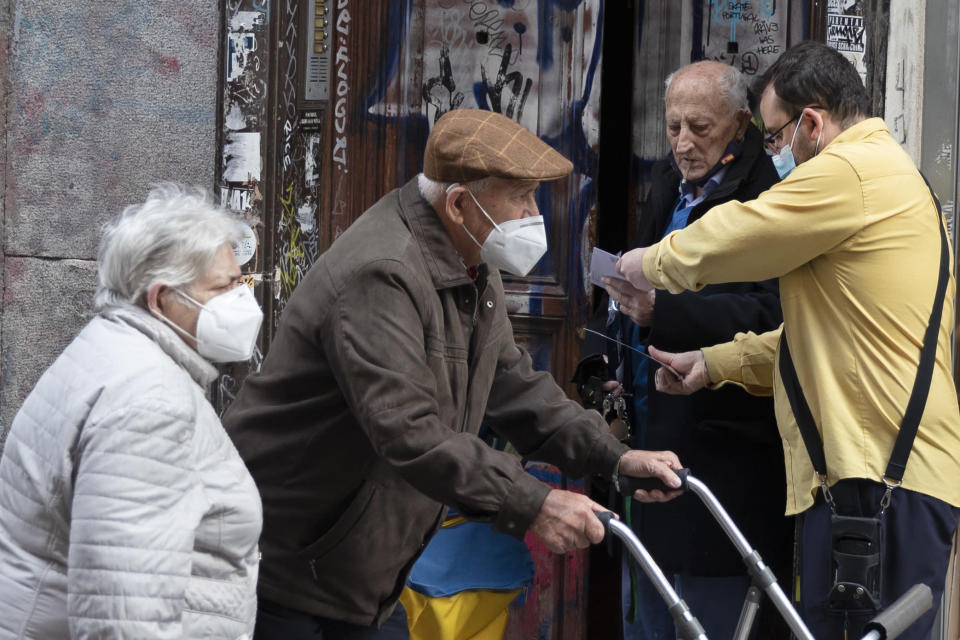 A man talks with a postman in a doorway as a couple wearing face masks to protect against the spread of coronavirus walk by in Madrid, Spain, Friday, Nov. 6, 2020. Restrictions are in force across the country as authorities try to contain a sharp resurgence of reported coronavirus cases but are refraining from a full lockdown to try to prevent further economic deterioration. (AP Photo/Paul White)