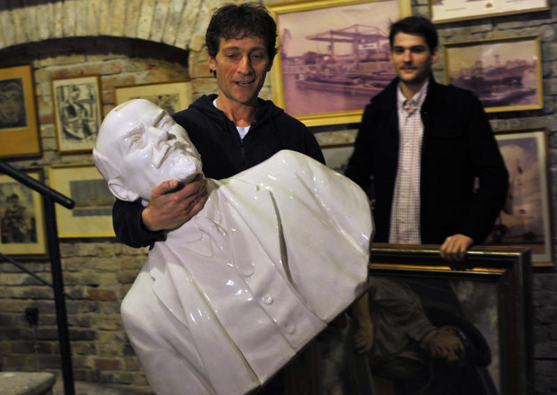 Staff member of the Pinter Gallery brings a large bust of Soviet revolutionary Vladimir Lenin into the basement of the gallery before its auction in Budapest, Hungary, Monday, Nov. 22, 2010. More than 200 pieces of communist era relics were found by the Hungarian government in various ministries and state warehouses and will be sold in early December to benefit the victims of last month's red sludge disaster. (AP Photo/Bela Szandelszky)
