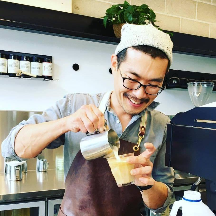 Yun-Seob Shin pours milk into a coffee while working in a cafe.