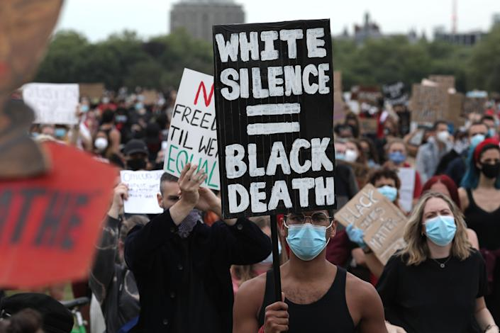 """<i>During a Black Lives Matter protest in London's Hyde Park on June 3, a protester holds up a sign that says """"White silence = Black death.""""</i>"""
