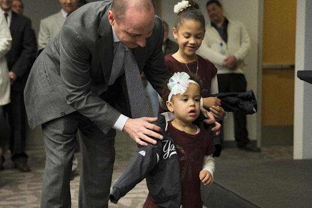 New York Yankees general manager Brian Cashman helps Kiera Beltran, daughter of Carlos Beltran, not pictured, put on a Yankees jacket as her sister Ivana looks on during a news conference at Yankees Stadium, Friday, Dec. 20, 2013, in New York. The former St. Louis Cardinals outfielder signed with the New York Yankees on a $45 million, three-year contract.(AP Photo/John Minchillo)