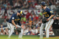 The ball drops between Milwaukee Brewers first baseman Rowdy Tellez (11) and Milwaukee Brewers starting pitcher Brandon Woodruff (53) during the seventh inning of Game 4 of a baseball National League Division Series against the Atlanta Braves, Tuesday, Oct. 12, 2021, in Atlanta. (AP Photo/Brynn Anderson)