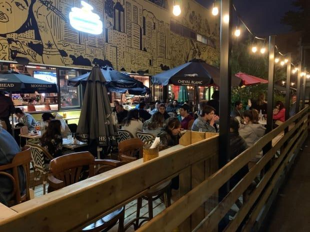 People waited in line to get a coveted spot on a newly reopened patio Friday night.