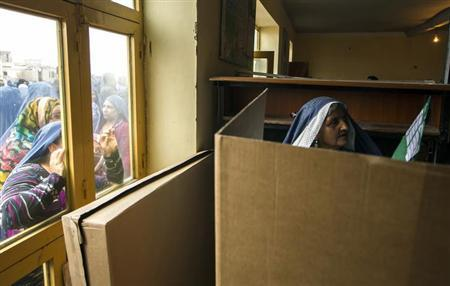 An Afghan woman gets help from women through a window while voting at a polling station in Mazar-i-sharif April 5, 2014. REUTERS/Zohra Bensemra