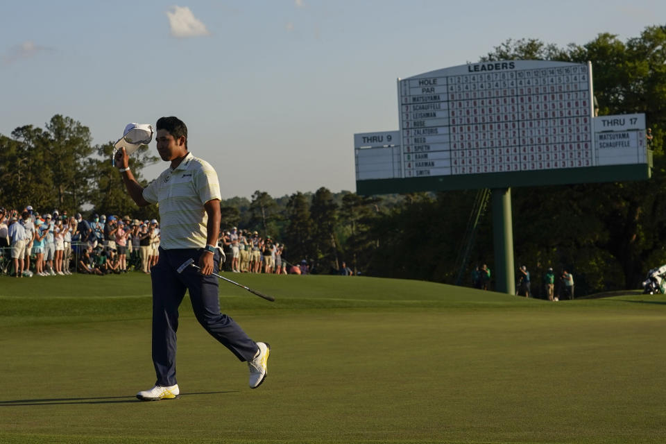 Hideki Matsuyama, of Japan, waves his cap after winning the Masters golf tournament on Sunday, April 11, 2021, in Augusta, Ga. (AP Photo/David J. Phillip)