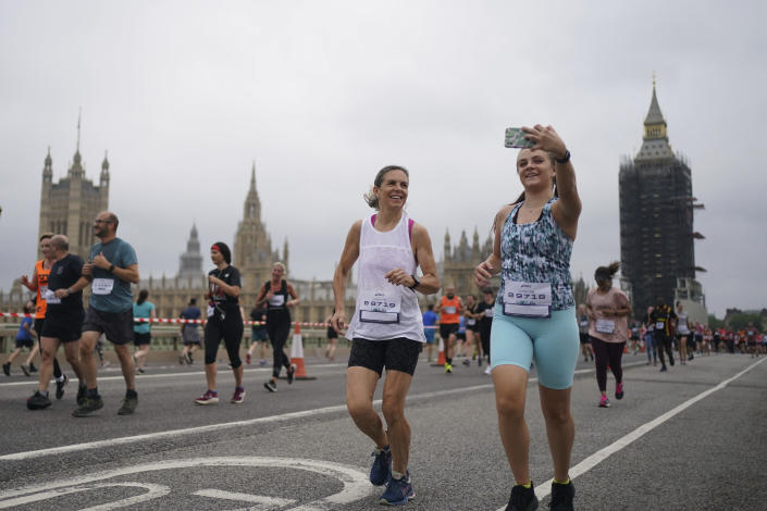 Participants run on Westminster Bridge, during the Asics London 10k, thought to be the largest closed road running event in London since the March 2020 lockdown, in London, Sunday July 25, 2021. (Victoria Jones/PA via AP)