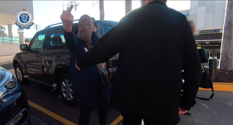 The woman flipped off her middle finger and swore as she exited a police vehicle. Source: NSW Police