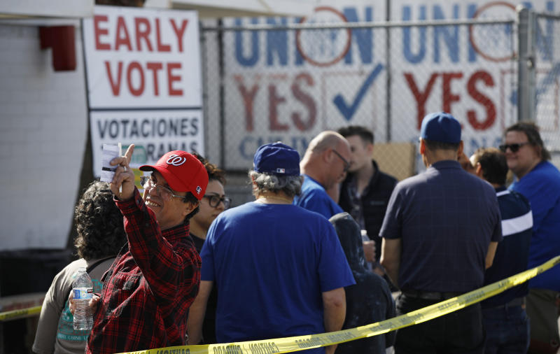 People wait in line to vote early at the Culinary Workers union Monday, Feb. 17, 2020, in Las Vegas. Nevada's first-in-the West presidential caucus puts the spotlight Saturday on a state that has swung increasingly blue over the last two decades. (AP Photo/John Locher)