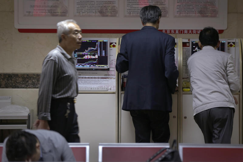 A man walks by investors check stock prices at a brokerage house in Beijing, Wednesday, April 24, 2019. Shares were mostly lower in Asia on Wednesday despite the S&P 500's all-time record high close the day before. (AP Photo/Andy Wong)