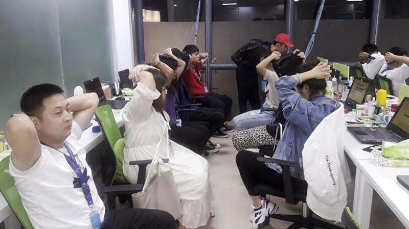 In this Oct. 9, 2019, photo provided by Philippine Bureau of Immigration, foreign nationals, mostly Chinese put their hands on their heads during a raid of their company premises in Manila, Philippines. Philippine police and immigration authorities said they have arrested more than 500 illegally working foreigners, mostly Chinese involved in telecommunications and investment scams, in one of the biggest such mass arrests this year. (Philippine Bureau of Immigration Via AP)