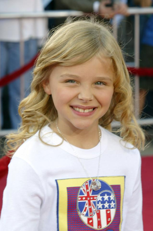 """<p>Can we get an """"awwwwww""""? Seven-year-old Chloë hit the red carpet for the premiere of <em>Dreamer</em> in 2005 with the look of a star in the making. While her face was appropriately bare, sweet curled locks and a silver pendant necklace added a bit of formal flair.</p>"""