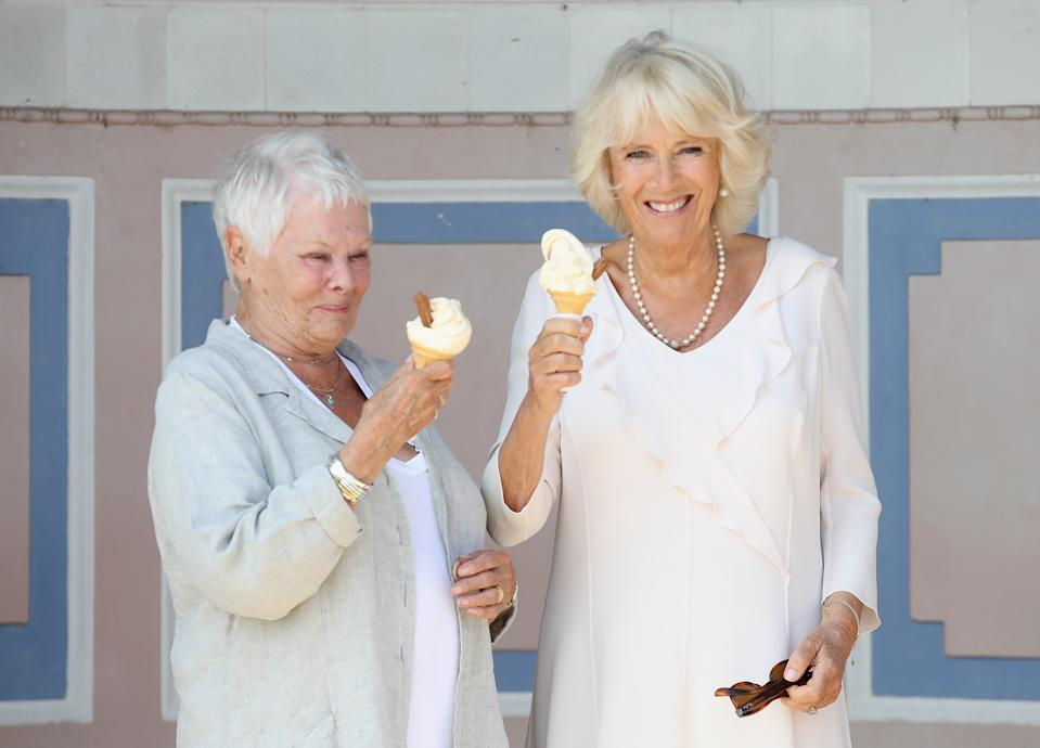 COWES, UNITED KINGDOM - JULY 24: Camilla, Duchess of Cornwall enjoys an ice cream with Dame Judi Dench as she arrives at Queen Victoria's private beach, next to the monarch's holiday home, during her visit to the Isle of Wight on July 24, 2018 in Cowes, Isle of Wight, United Kingdom. (Photo by Andrew Matthews - WPA Pool/Getty Images)
