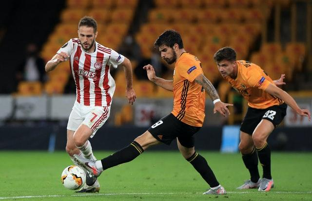 Ruben Neves and Olympiacos' Kostas Fortounis battle for the ball