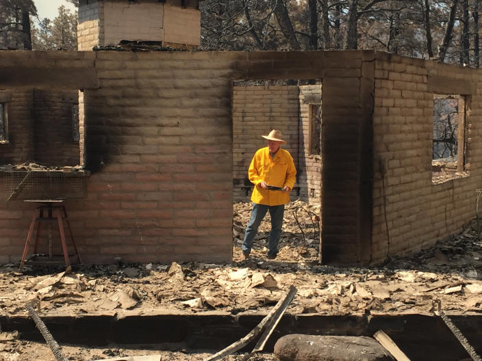 In this photo provided by Rusty Bowers, Arizona House Speaker Rusty Bowers walks through the remains of his family's weekend home on Tuesday, June 8, 2021, that was destroyed by a wildfire the day before. Bowers used the home in the remote mountains as a family retreat and often did his artwork there. (Elijah Cardon/Rusty Bowers via AP)