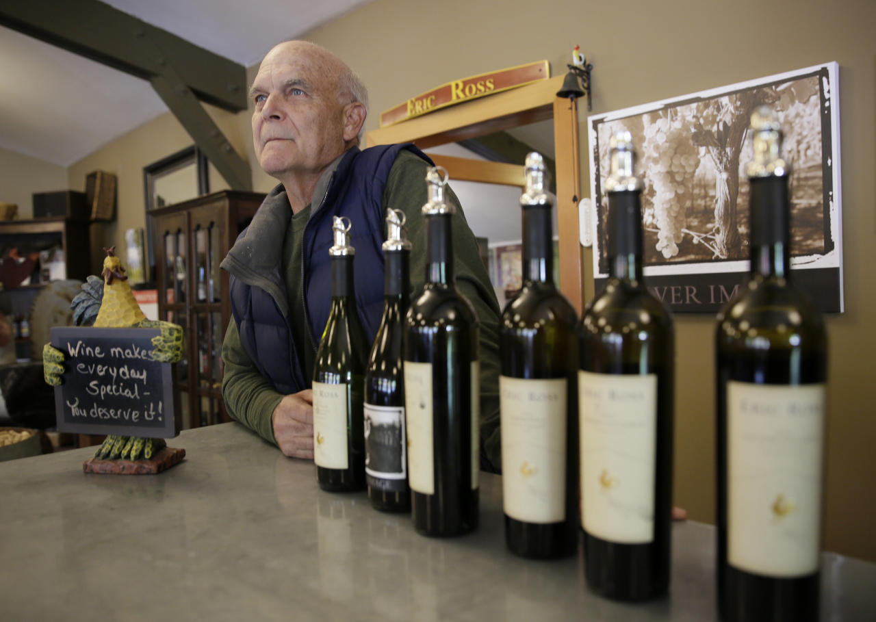 """In this photo taken Monday, Oct. 30, 2017, winemaker Eric Luse stands behind the tasting room counter at his Eric Ross Winery in Glen Ellen, Calif. Once people understand everything is not burned down, tourism will return within a few months, said Luse. """"If you're not optimistic, you are in the wrong business."""" (AP Photo/Eric Risberg)"""