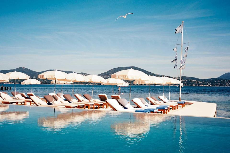 A pool by the sea, surrounded by white deck chairs and umbrellas