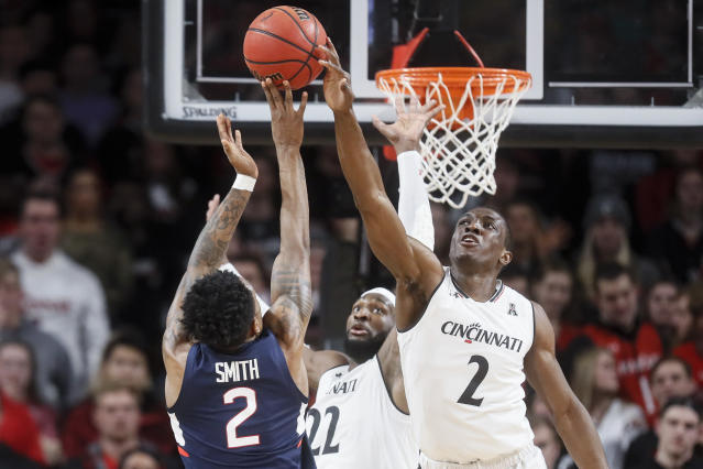 Cincinnati's Keith Williams, right, blocks a shot by Connecticut's Tarin Smith, left, in the first half of an NCAA college basketball game, Saturday, Jan. 12, 2019, in Cincinnati. (AP Photo/John Minchillo)