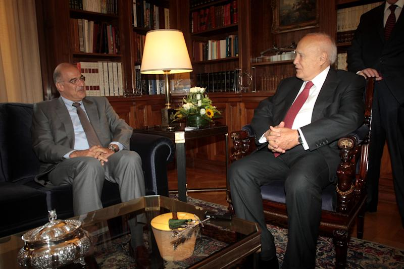 Greek President Karolos Papoulias, right, speaks with minister of public order Nikos Dendias, at the presidential palace in Athens, Tuesday, Sept. 24, 2013. Authorities said the police's internal affairs division were searching the precincts at Nikea and two other nearby locations after the government ordered an emergency inquiry into activities of the far-right Golden Dawn party and alleged ties to law enforcement officials. (AP Photo/Fosphotos/Panagiotis Tzamaros)