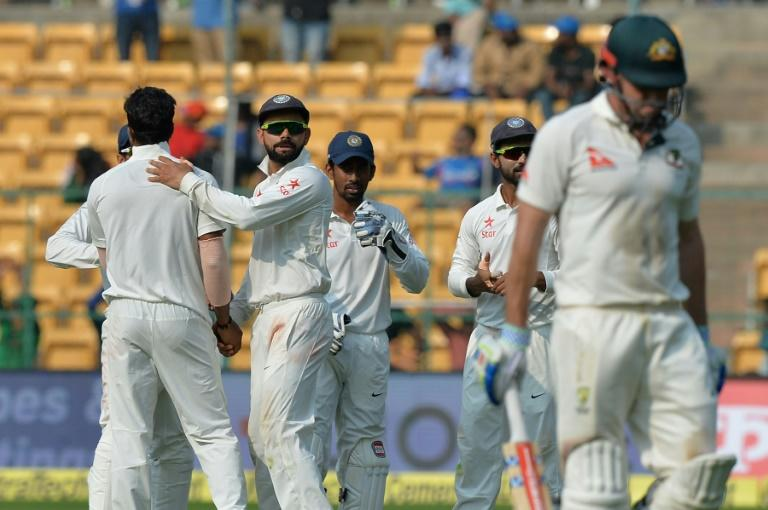India captain Virat Kohli (2L) congratulates bowler Umesh Yadav (L) for dismissing Australia batsman Shaun Marsh (R) on the second day of the second Test at The M. Chinnaswamy Stadium in Bangalore on March 5, 2017