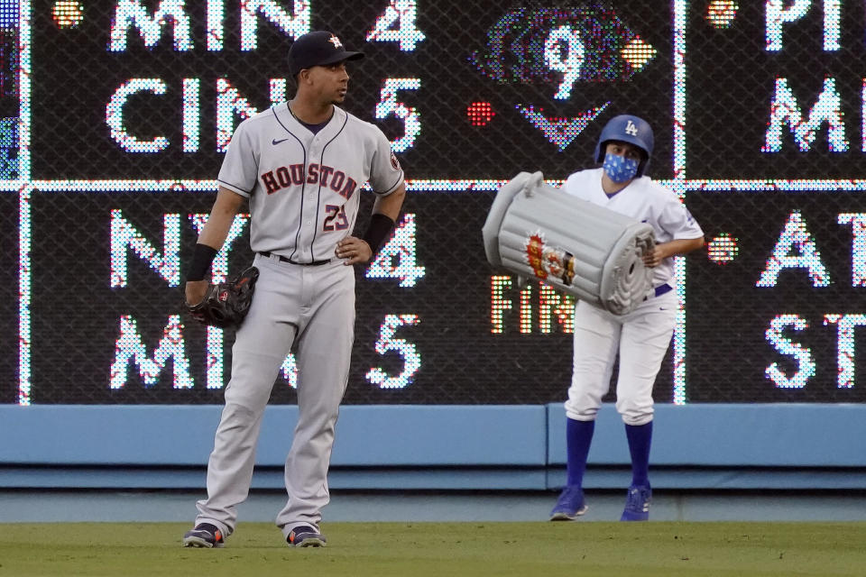 A ball girl removes an inflatable item in the shape of a trash can behind Houston Astros right fielder Michael Brantley during the first inning of the Astros' baseball game against the Los Angeles Dodgers on Tuesday, Aug. 3, 2021, in Los Angeles. (AP Photo/Marcio Jose Sanchez)