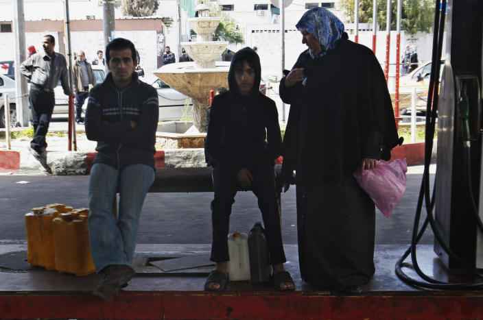Palestinians wait to fill up canisters with fuel at a gas station in Gaza City, Wednesday, March 21, 2012. A test of wills between Egypt and Gaza's Hamas government has produced the worst energy crisis here in years: Gazans are enduring 18-hour-a-day blackouts and the fuel supply is running low. (AP Photo/Adel Hana)