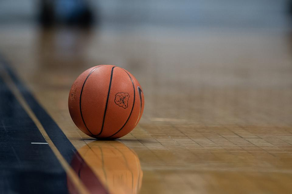 A basketball sits alone on the court.